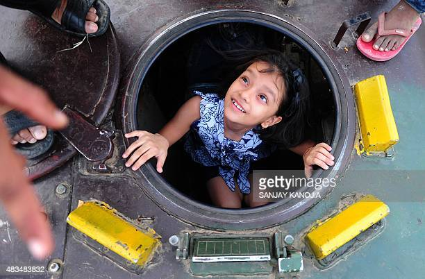 An Indian girl looks up from an army tank during the second day of the 'Know Your Army' exhibition in Allahabad on August 9 2015The exhibition aims...