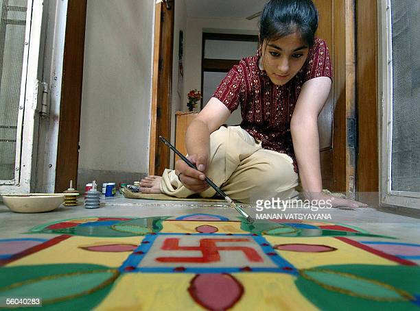 An Indian girl paints rangoli or coloured designs at her home in New Delhi 01 November 2005 on the day of the Hindu festival Diwali The festival...