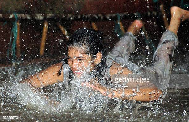 An Indian girl plays in the water from an unexpected rainfall in Hyderabad 08 May 2006 The rain brought temporary relief from a blistering heatwave...