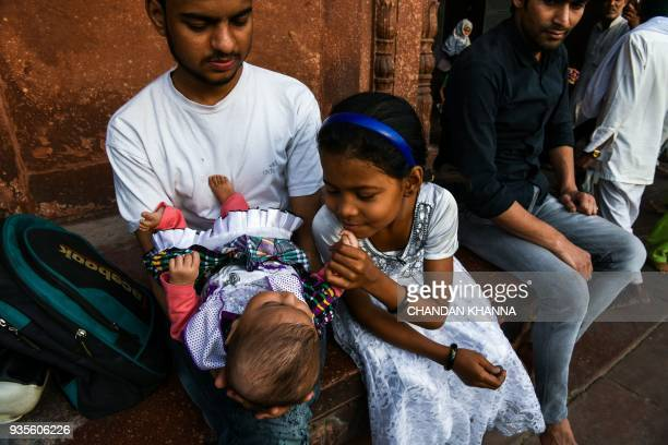 An Indian girl plays with her baby sister inside Jama Masjid with her mother in the old quarters of New Delhi on March 21 2018 / AFP PHOTO / CHANDAN...