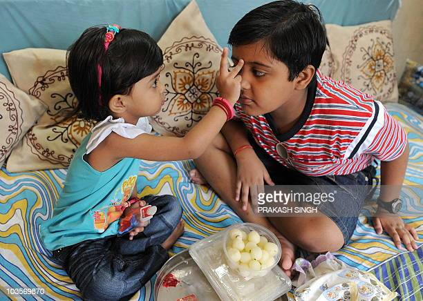An Indian girl puts a Tikka on the forehead of her brother prior to tying a rakhi or sacred thread around his wrist on the occasion of Raksha Bandhan...