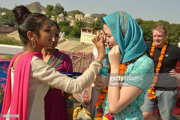 An Indian girl putting bindi on a foreigner's forehead during the celebration of 'World Tourism Day' with cultural programs organised by respective...