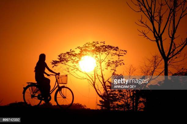 TOPSHOT An Indian girl rides a bicycle during sunset in Joypur village on the outskirts of Agartala the capital of northeastern state of Tripura on...