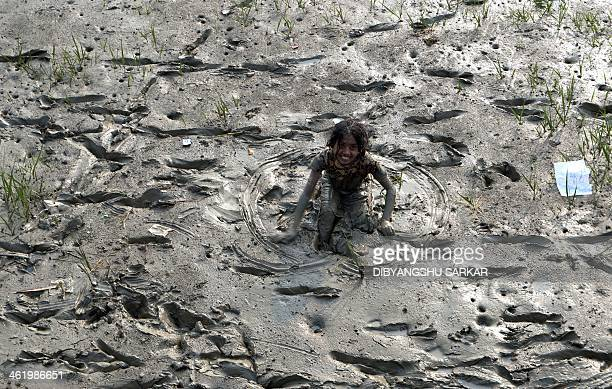 An Indian girl runs through the mud to ask for alms from pilgrims heading for ferries to cross the Hoogly river on their way to Gangasagar Mela in...