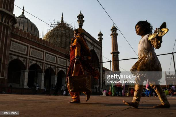 An Indian girl walks inside Jama Masjid with her mother in the old quarters of New Delhi on March 21 2018 / AFP PHOTO / CHANDAN KHANNA