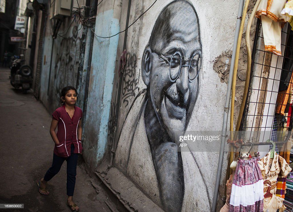 An Indian girl walks past a graffiti painting of Mahatma Gandhi in an alleyway in New Delhi on March 17, 2013. Indian business leaders and the government have for months been calling for lower lending rates to help the once-booming economy, forecast to see a five percent growth rate in the year to March 2013, the weakest in a decade. AFP PHOTO/ Andrew Caballero-Reynolds