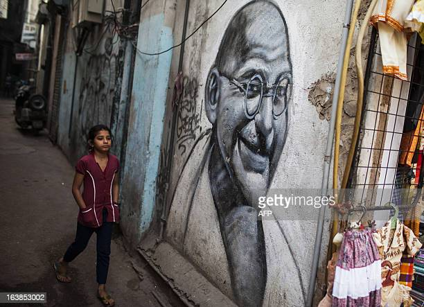 An Indian girl walks past a graffiti painting of Mahatma Gandhi in an alleyway in New Delhi on March 17 2013 Indian business leaders and the...