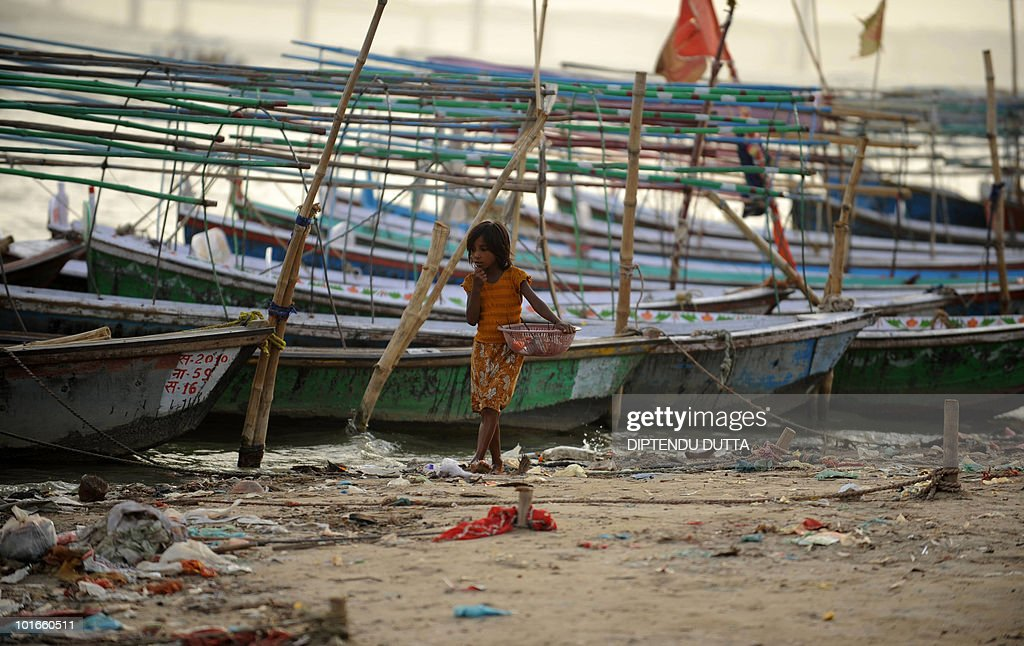 An Indian girl walks past fishing boats at Sangam, the confluence of the Ganges, Yamuna and Saraswati rivers in Allahabad on June 6, 2010. The meteorological department has forecasted a normal monsoon this year which will help boost the agricultural output and bring down the rising food inflation. AFP PHOTO/Diptendu DUTTA