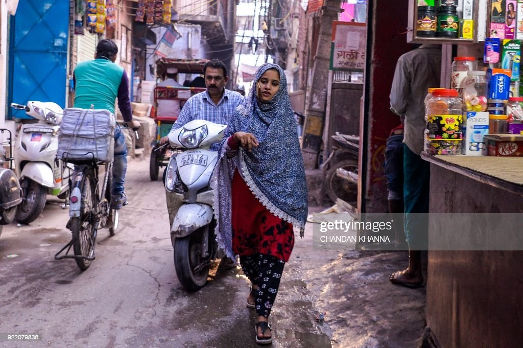 An Indian girl walks through the old quarters of New Delhi on February 21, 2018