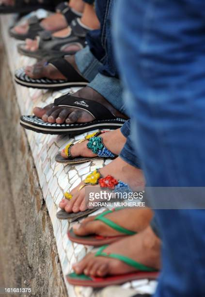 An Indian girl wears slippers decorated with artificial fowers as she stands on a parapet wall along with her male friends as they watch a flash mob...