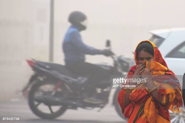 An Indian girl with her face covered walks on a street amid heavy smog in New Delhi on November 13 2017 Schools reopened in New Delhi on November 13...