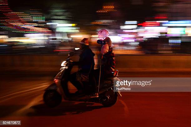 An indian girldressed as santa clauserides a scooter as other holds balloonson ocassion of Christmasin Allahabad on December 252015