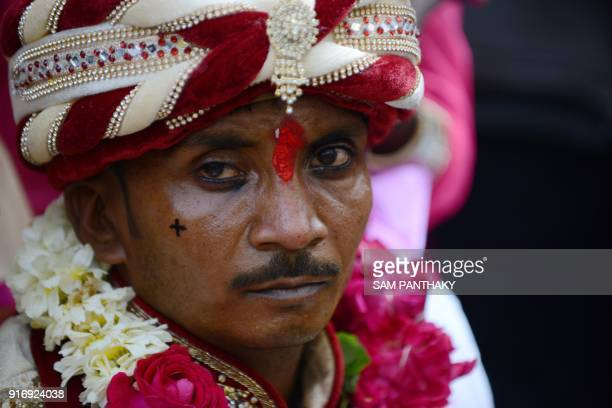 An Indian groom looks on during a mass wedding for members of the Adivasi Bhil tribal community in Ahmedabad on February 11 2018 Some 35 couples were...