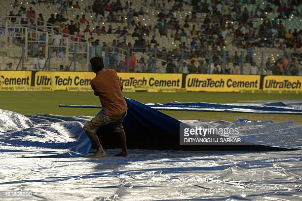 An Indian groundstaff member removes covers from the playing surface ahead of the start of the third T20 cricket match between India and South Africa...