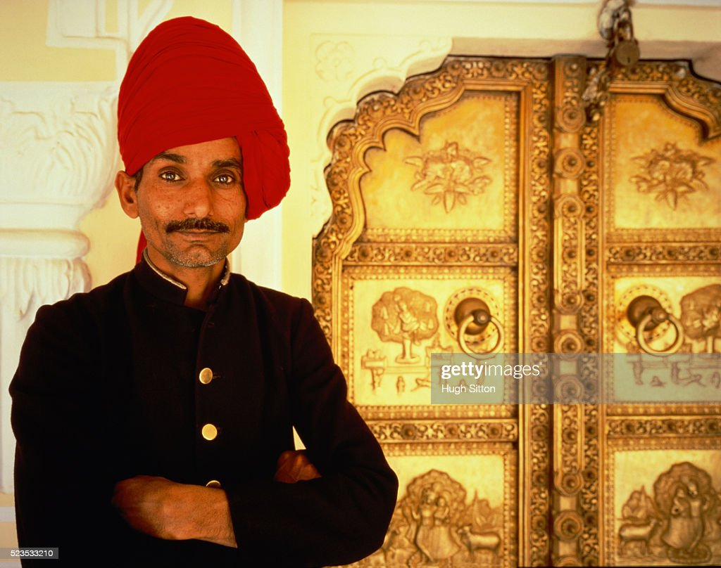 An Indian guardsman standing in front of a golden door, India, Jaipur, City Palace, half port : Stock Photo