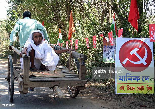 An Indian handcart driver conveys an elderly woman voter towards a polling station in the village of Jirania some 20kms east of Agartala on February...