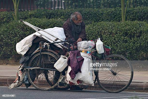 An Indian handicapped homeless man carries his belongings on a tricycle in New Delhi on January 14 2014 Delhi has a homeless population of more than...