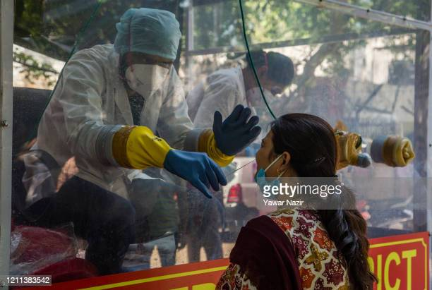 An Indian health official inside a COVID-19 mobile testing van uses a nasal swab to collect a sample from a woman, as India remains under an...