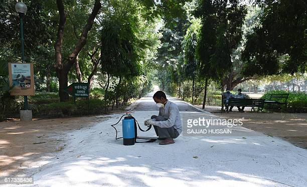 An Indian health worker adjusts a mchine before he sprays pesticides inside the Deer Park which is temporarily closed for visitors as a precautionary...