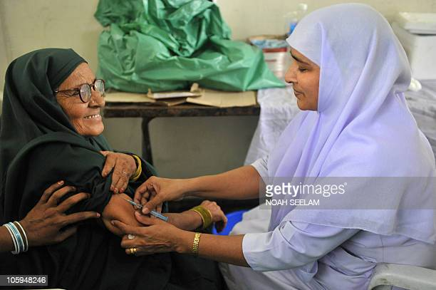 An Indian health worker administers a meningococcal polysaccharide vaccine to a Haj pilgrim in Hyderabad on October 22 as she prepares to depart for...