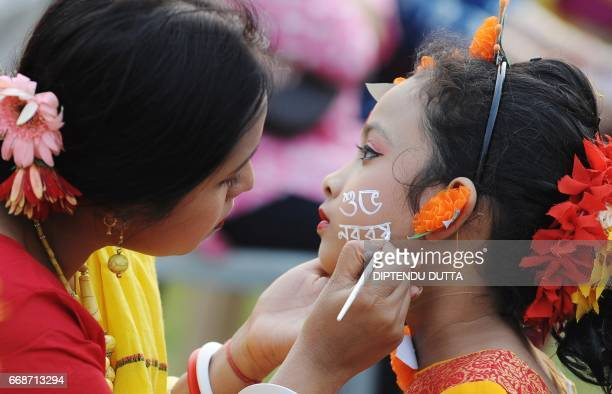An Indian Hindu Bengali woman paints the face of a girl with a 'Suvo Nabarsho' message during celebrations to mark Bengali New Year in Siliguri on...