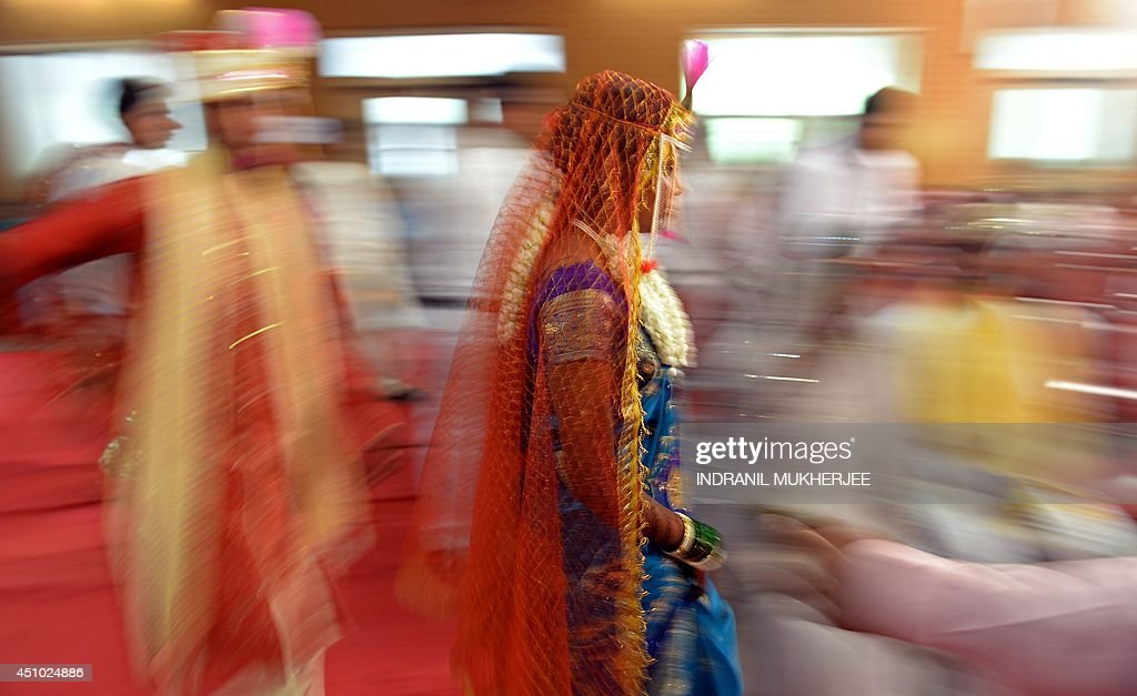 An Indian Hindu bride and groom arrive for a multi-faith mass wedding in Mumbai on June 22, 2014. Over 50 underprivileged couples from different communities were wedded according to the traditions of their faith on the occassion. Mass marriages generally organised by social organisations to cut ceremony costs are common in India with its billion plus population where the custom of dowry and expensive gifts from the bride's family still prevails among certain segments of society.