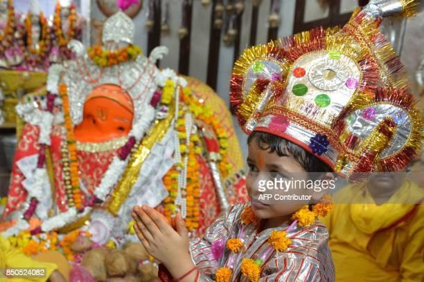An Indian Hindu child dressed as a Langur monkey to honour the Hindu monkeygod Hanuman pays a visit to Bara Hanuman Temple in Amritsar on September...