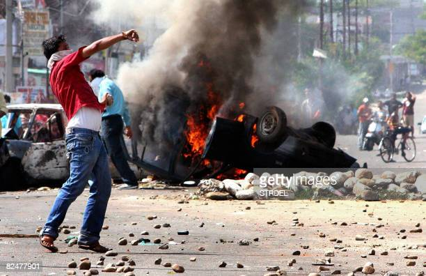 An Indian Hindu demonstrator throws stones toward the police during a protest against the revoking of an order awarding land to a Hindu pilgrimage...