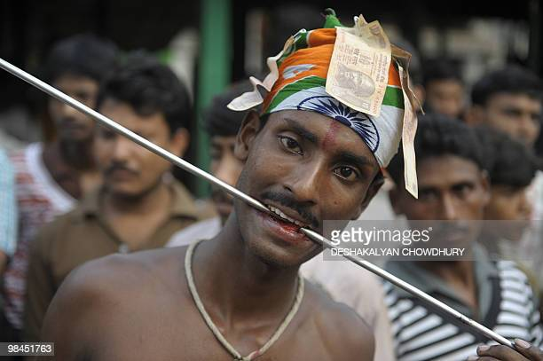 An Indian Hindu devotee adjusts a metal rod pierced through his tongue during the ritual of Shiva Gajan at a village in Bainan some 80 kms south of...