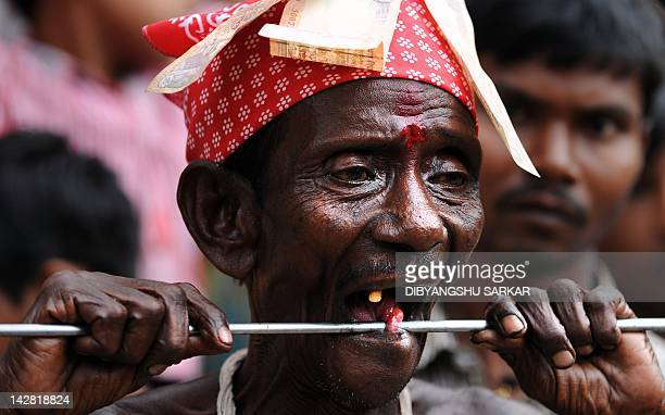 An Indian Hindu devotee adjusts a metal rod piercing his tongue as villagers look on during the ritual of Shiva Gajan at a village in Bainan some 80...