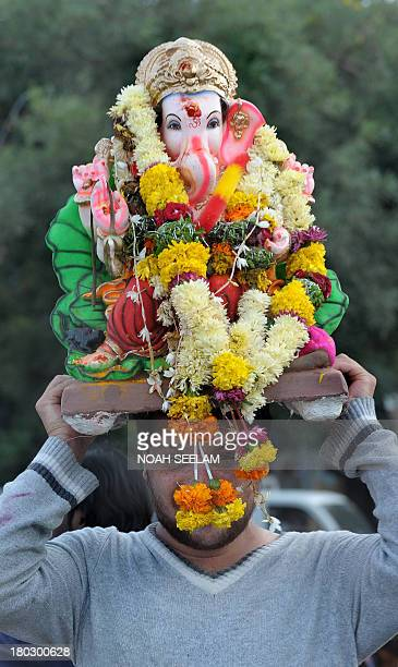 An Indian Hindu devotee carries an idol of elephantheaded Hindu god Ganesha for immersion at Hussain Sagar Lake on the third day of the tenday long...