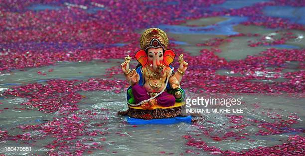 An Indian Hindu devotee carries an idol of elephantheaded Hindu god Ganesha for immersion inside an environmentally friendly artificial water tank on...