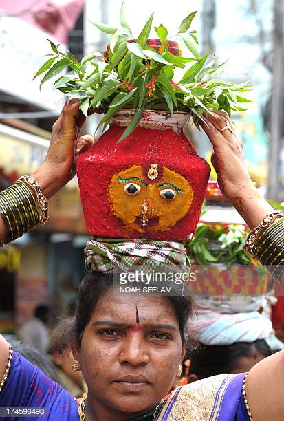 An Indian Hindu devotee carries 'ghatam' a pot filled with cooked rice and decorated with neem leaves during the festival of Bonalu a ritual offering...