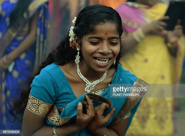 An Indian Hindu devotee chants as a traditional sweet dish is cooked on open fires during a community function on the occasion of Pongal in Mumbai on...