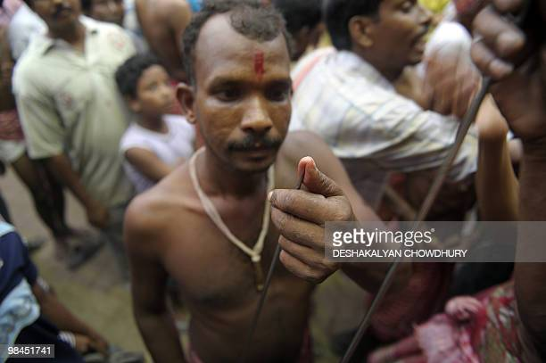 An Indian Hindu devotee checks the tip of a metal rod before using it to pierce his tongue during the ritual of Shiva Gajan at a village in Bainan...