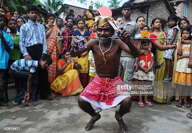 An Indian Hindu devotee dances after having his tongue pierced with a metal rod as a crowd of people watch during the ritual of Shiva Gajan at a...