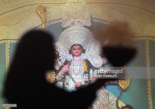An Indian Hindu devotee dances in front of idols of Goddess Durga during the Durga pooja festival in Mumbai on October 15 2010 The five day worship...