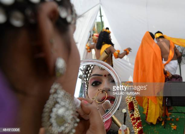 An Indian Hindu devotee dressed as a deity puts on makeup ahead of a procession in New Delhi on April 15 on the occasion of Hanuman Jayanti the...