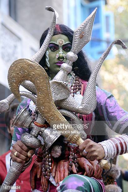 An Indian Hindu devotee dressed as Goddess Kali Mata participates in a procession in Amritsar on November 12 on the occasion of the birth anniversary...