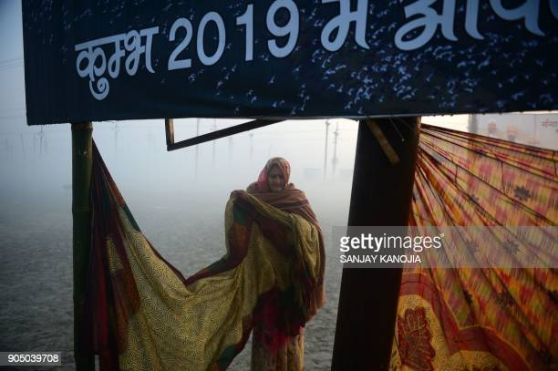 TOPSHOT An Indian Hindu devotee dries a sari after bathing during the annual 'Magh Mela' gathering at Sangam the confluence of the rivers Ganges...