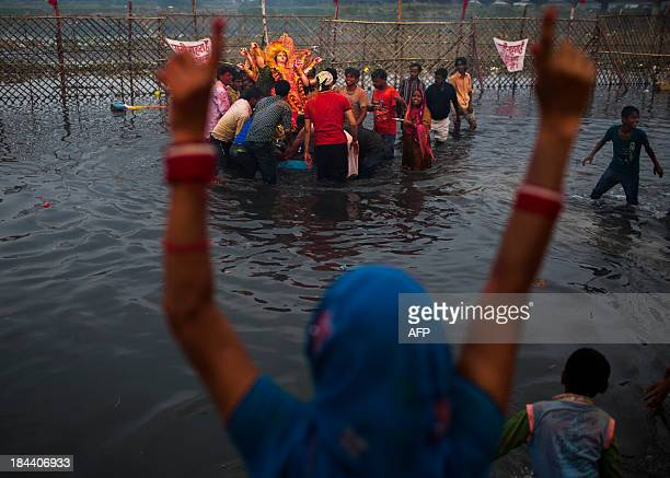 An Indian Hindu devotee gestures as other devotees immerse an idol in the Yamuna river as part of the Durga Puja festival in New Delhi on October 13...