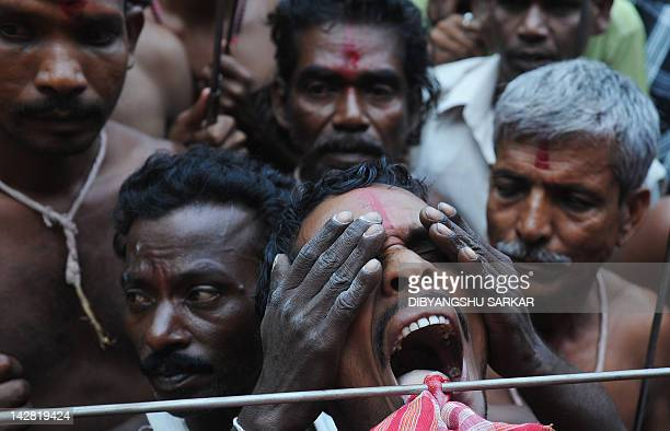 An Indian Hindu devotee has his tongue pierced with a metal rod by a priest during the ritual of Shiva Gajan at a village in Bainan some 80 kms south...