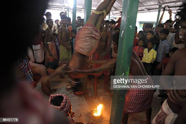 An Indian Hindu devotee is swung by others as he hangs himself upside down over a fire during the ritual of Shiva Gajan at a village in Bainan some...
