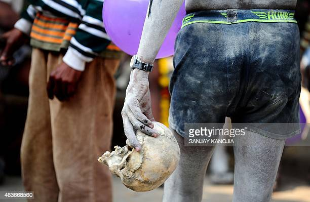An Indian Hindu devotee of Lord Shiva holds a human skull during a religious procession to mark the Hindu festival of Maha Shivratri in Allahabad on...