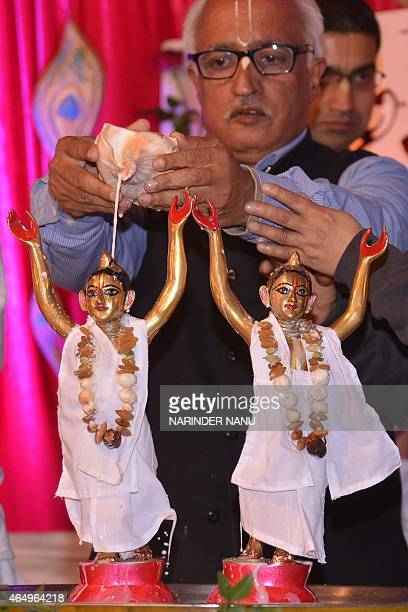 An Indian Hindu devotee of The International Society of Krishna Conciousness pours milk onto idols of Hindu Lord Krishna and his elder brother...