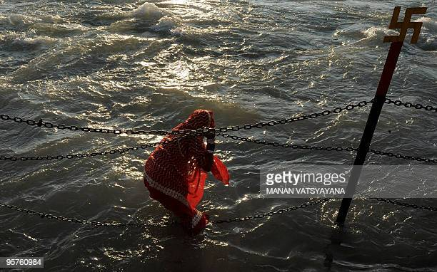 An Indian Hindu devotee offers prayers while bathing in the river Ganges in Haridwar on January 14, 2010 during the Kumbh Mela festival , on one of...