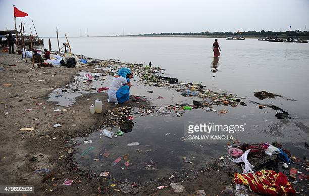 An Indian Hindu devotee performs a ritual near the polluted waters of the river Ganga as the level rises at Sangam the confluence of the Ganga Yamuna...