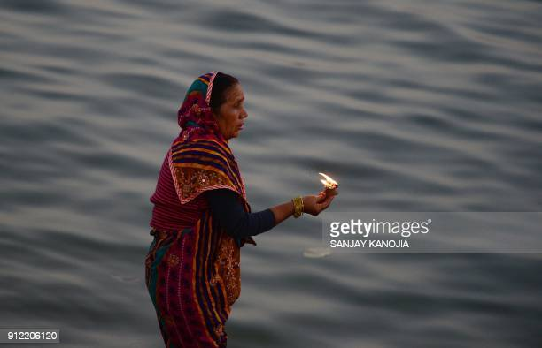 An Indian Hindu devotee performs evening prayers at Sangam the confluence of the rivers Ganges Yamuna and mythical Saraswati during the annual Magh...