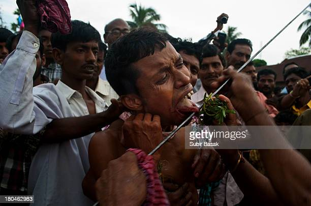 An Indian Hindu devotee pierced his tongue with a metal rod as a part of their ritual during the festival of Shiva Gajan in the village of...