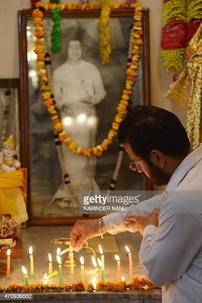 An Indian Hindu devotee poses for a photograph as he lights candles and offers prayers on the fourth death anniversary of Sri Satya Sai Baba at a...